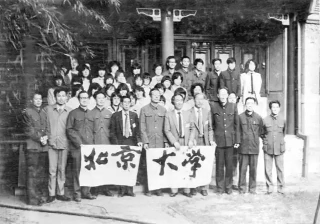 """北京大学燕园书画会与日本书道学校代表团在临湖轩交流结束后合影。""""北京大学""""四字由李志敏题写。前排左二为华人德、左三为罗荣渠、左六为李志敏、左七为小林抱牛,右二为陈玉龙。第二、三、四排靠左皆为日本代表团成员。"""