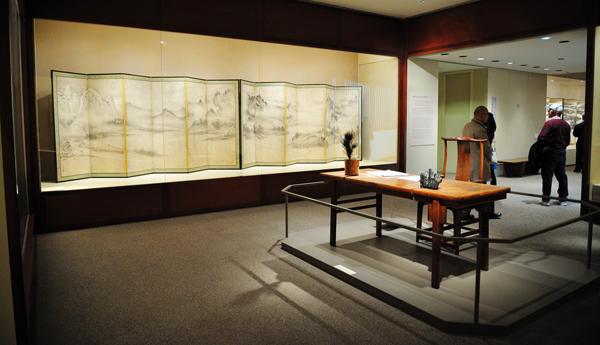 大都会艺术博物馆日本展厅内一景。前景是明代的黄花梨木桌,上面摆着的是清代的笔筒和灵璧石摆件,后面是明代晚期的黄花梨木椅。展橱内为室町时代山水画家相阿弥的《潇湘八景图卷》屏风。16世纪早期,宽370.8cm。 图片采集自情枭的黎明论坛帖。 缩图