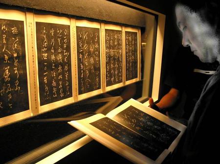 9月24日,一位书法爱好者在展厅里仔细研读王羲之的法帖。新华社记者 任珑 摄
