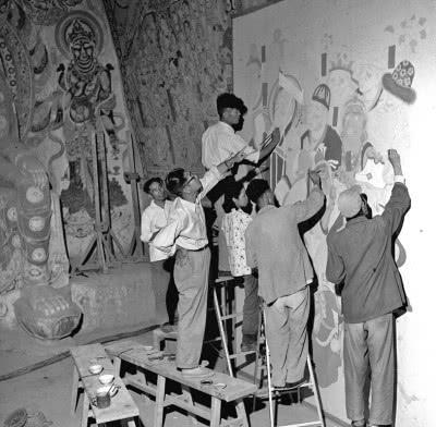 1959年10月,画家常书鸿(左二)在指导敦煌文物研究所工作人员临摹壁画。郝常耕摄